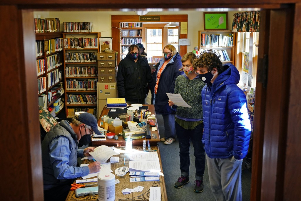John Zavodny, president of the Maine Seacoast Mission, left, registers residents for COVID-19 vaccinations in a library on the island of Islesford, Ma...