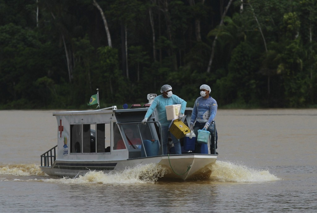 Healthcare workers Diego Feitosa Ferreira, 28, right, and Clemilton Lopes de Oliveira, 41, travel on a boat to the Santa Rosa community, Amazonas stat...