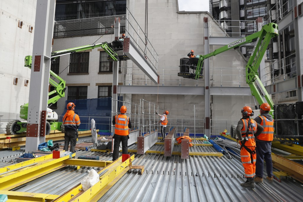 Construction workers lift a Steele beam into position at the 8 Bishopsgate development in London, Thursday, April 1, 2021. When the pandemic struck, a...