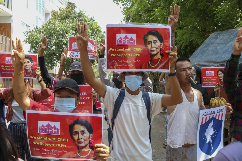 Anti-coup protesters flash the three-fingered symbol of resistance while holding slogans bearing pictures of deposed leader Aung San Suu Kyi during a ...