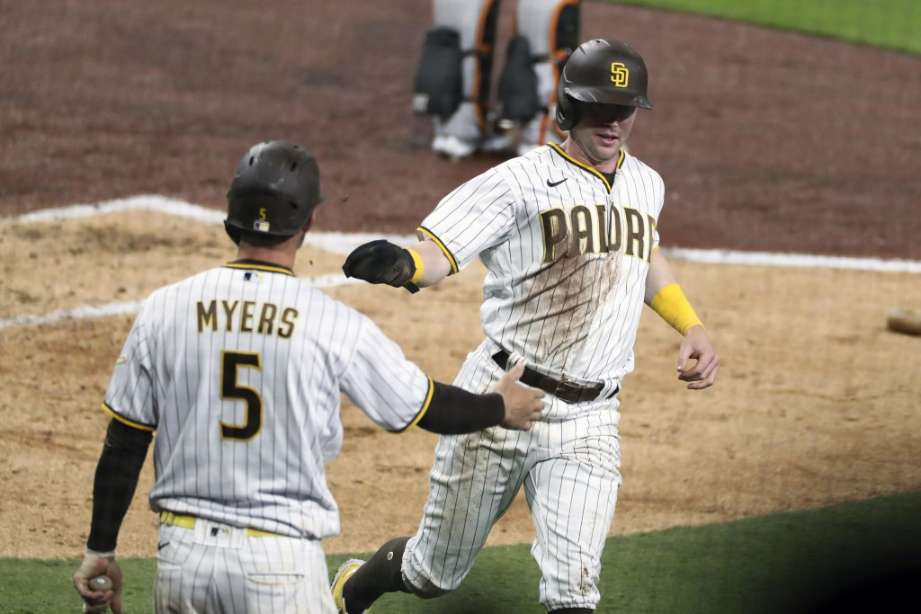 San Diego Padres Jake Cronenworth, right, is congratulated by Wil Myers, left, after scoring on an Eric Hosmer base hit against the San Francisco Gian...