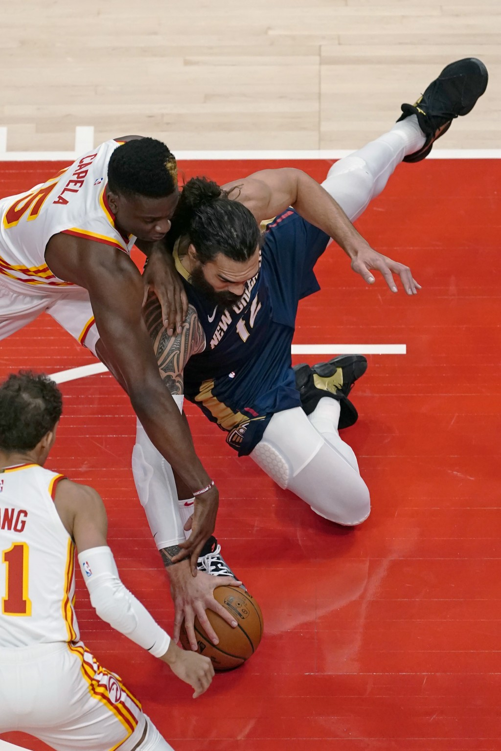 New Orleans Pelicans center Steven Adams (12) and Atlanta Hawks center Clint Capela (15) chase a loose ball in the first half of an NBA basketball gam...