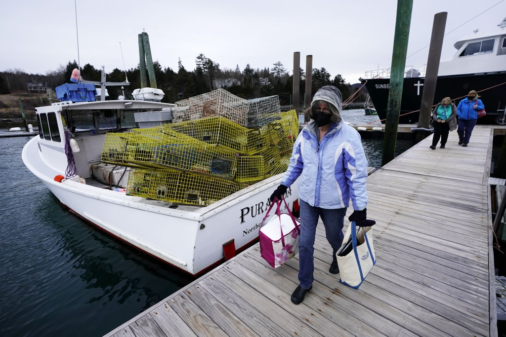 Nurse Sharon Daley carries a cooler of COVID-19 vaccinations as she and her staff begin a journey to inoculate island residents, Friday, March 19, 202...