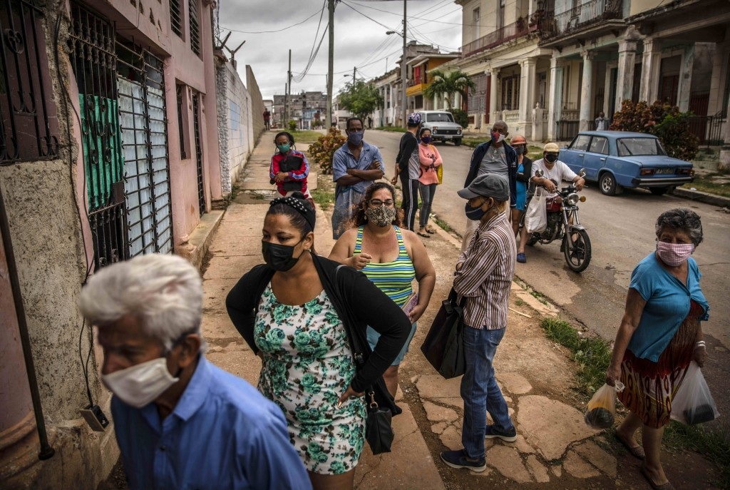 Yuliet Colon, center in tank top, waits her turn outside an agricultural market in Havana, Cuba, Friday, April 2, 2021. Colon is among several Cubans ...