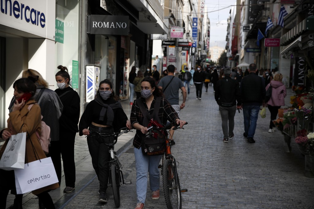Two young women wearing face mask to protect from the spread of coronavirus, walk with their bicycles on Ermou Street, Athens' main shopping area, Tue...