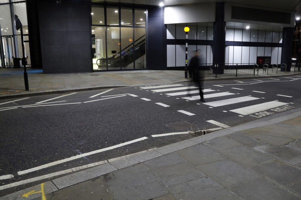 A man walks on a pedestrian crossing in London, Saturday, March 6, 2021. When the pandemic struck, about 540,000 workers vanished from London's financ...