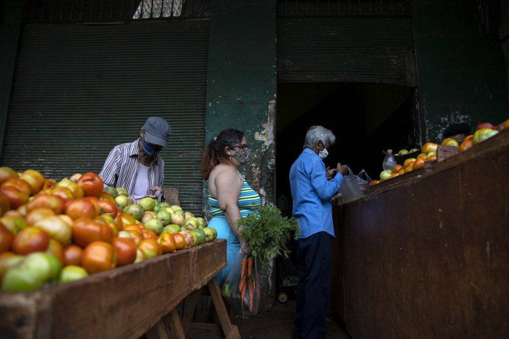 Yuliet Colon, center, waits to check-out at an agricultural market near her home, in Havana, Cuba, Friday, April 2, 2021. Colon is among several Cuban...