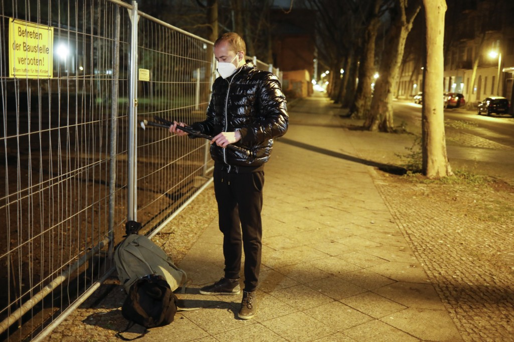 Brazilian activist and artist Rafael Puetter prepares himself prior to his one-man protest through Berlin, Germany, late Tuesday, April 6, 2021. The m...