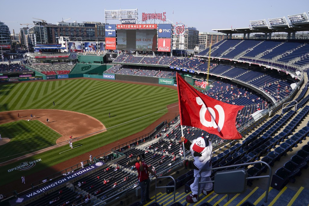 Washington Nationals mascot Screech waves a flag in the stands as fans sit socially distanced during an opening day baseball game between the National...