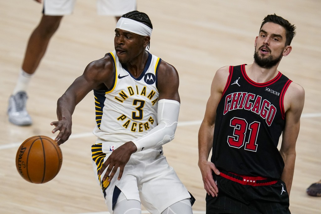 Indiana Pacers guard Aaron Holiday (3) passes the ball away from Chicago Bulls guard Tomas Satoransky (31) during the first half of an NBA basketball ...