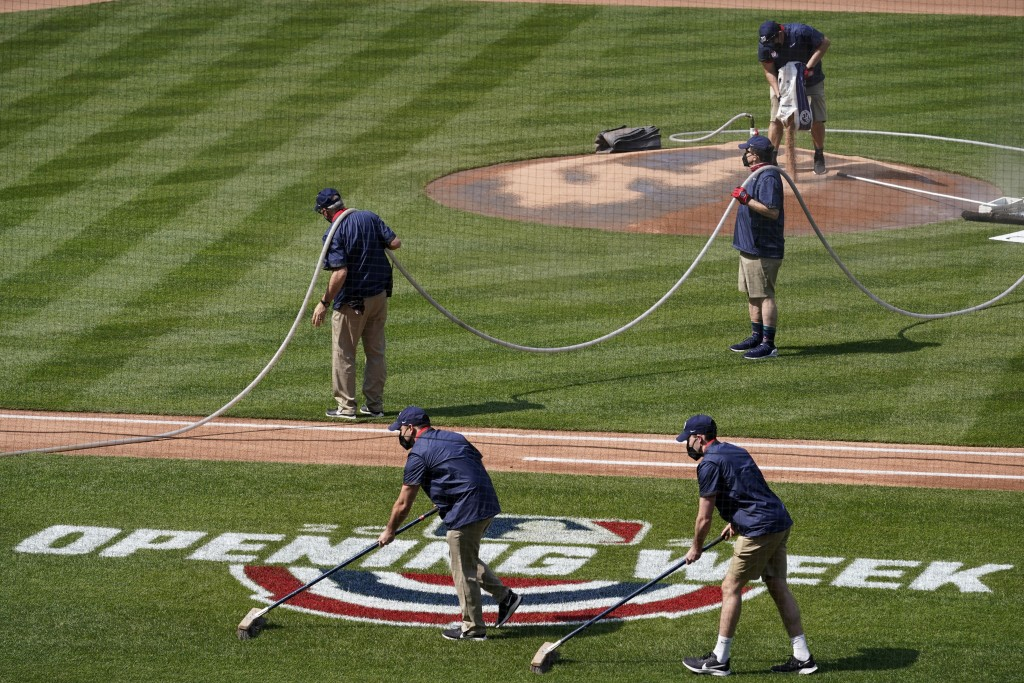 Groundskeepers prepare the field before a home opener baseball game between the Atlanta Braves and the Washington Nationals at Nationals Park, Tuesday...