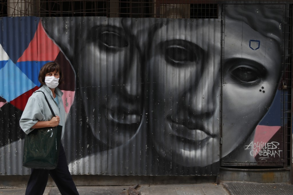 A woman wearing a face mask to protect from the spread of coronavirus, stands in front of a graffiti by the Greek artist Achilles in Athens, Tuesday, ...