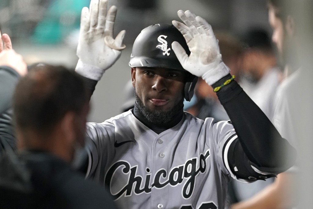 Chicago White Sox's Luis Robert is greeted in the dugout after he hit a two-run home run during the fifth inning of the team's baseball game against t...