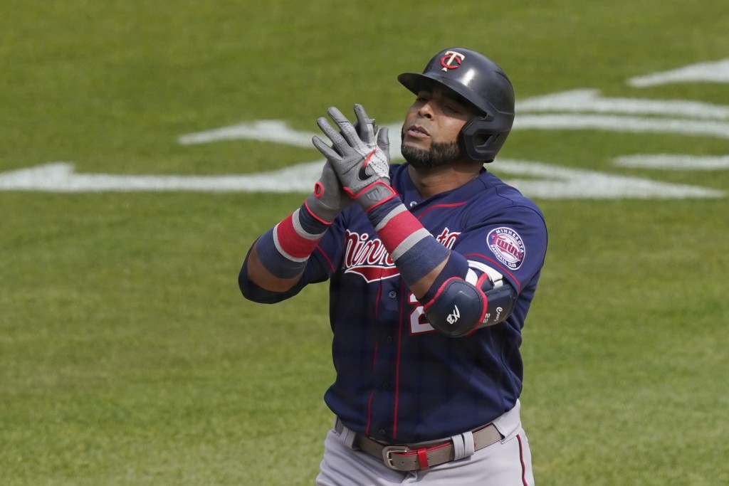 Minnesota Twins designated hitter Nelson Cruz reaches at home plate after a solo home run during the seventh inning of a baseball game against the Det...