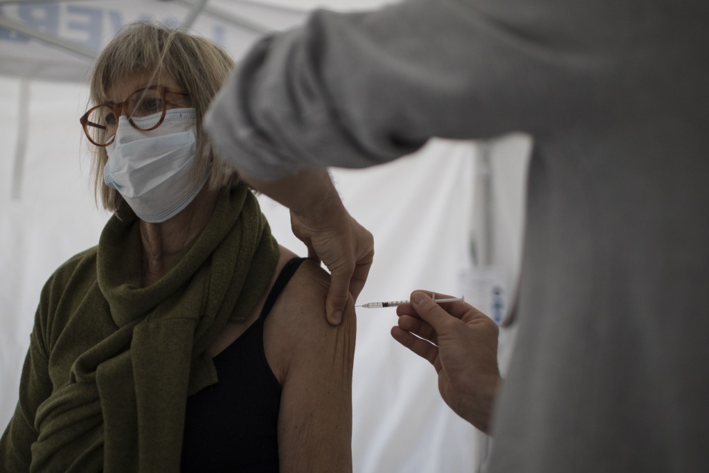A woman receives the Pfizer COVID-19 vaccine at the Laveran Military Hospital in Marseille, southern France, Wednesday, April 7, 2021. Seven military ...