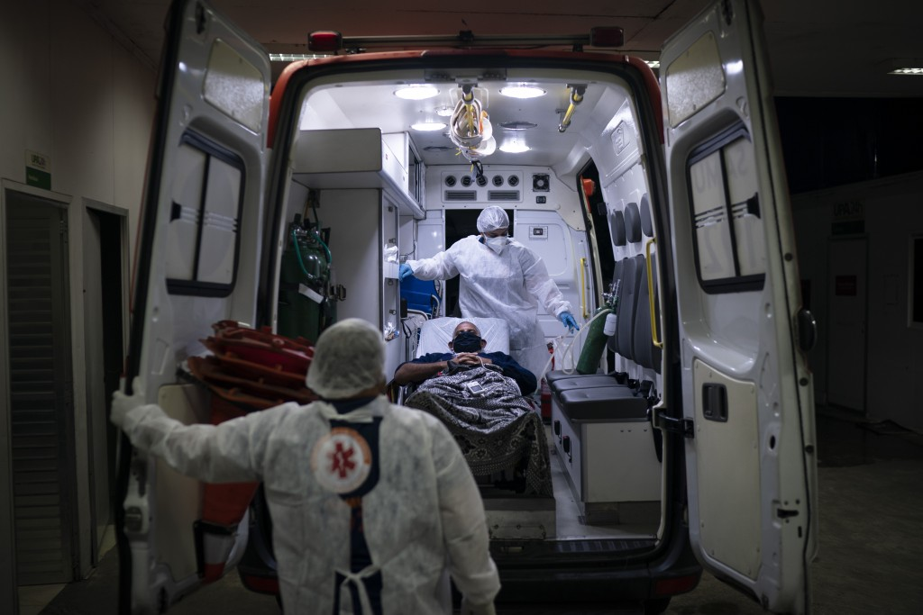 Mobile Emergency Care Service (SAMU) workers Gabrielle Carlos, top, and Joao Vericimo, move a COVID-19 patient to an ambulance as he is transferred to...
