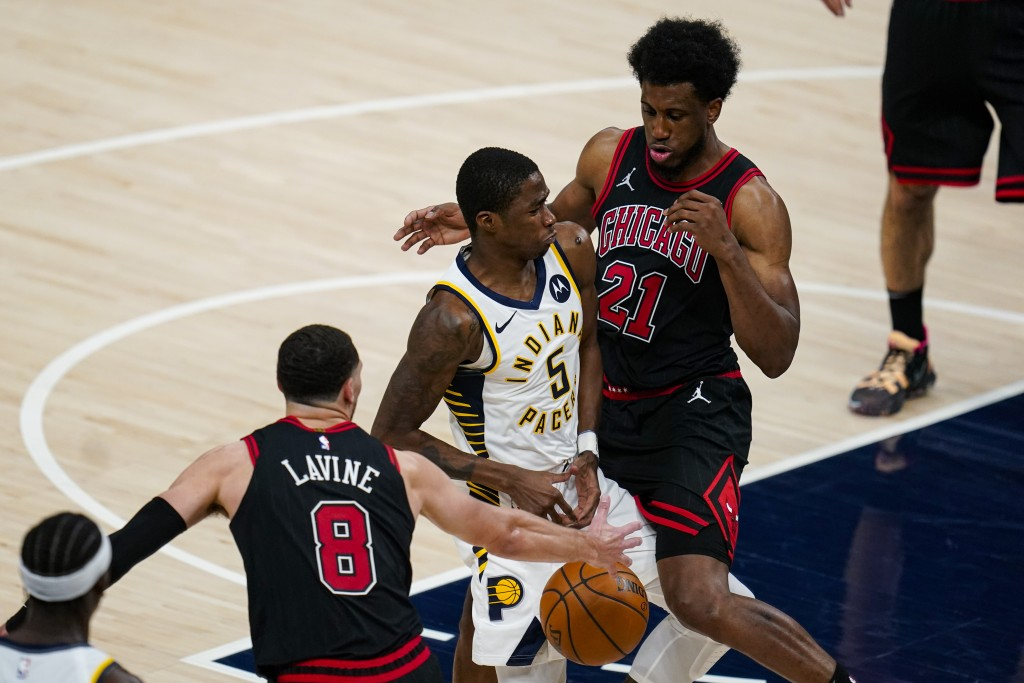 Indiana Pacers guard Edmond Sumner (5) loses the ball as he drives between Chicago Bulls guard Zach LaVine (8) and forward Thaddeus Young (21) during ...