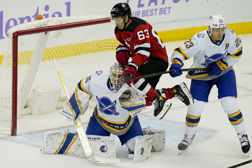 New Jersey Devils left wing Jesper Bratt (63) collides with Buffalo Sabres goaltender Michael Houser (35) during the first period of an NHL hockey gam...