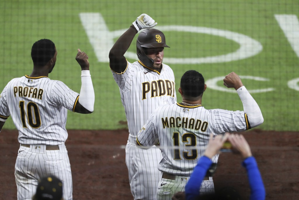 San Diego Padres' Victor Caratini, center, is congratulated by Manny Machado, right, after hitting a two-run home run against the San Francisco Giants...