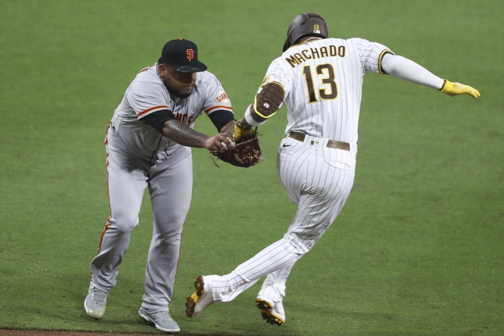 San Francisco Giants relief pitcher Reyes Moronta tags out San Diego Padres' Manny Machado during the sixth inning of a baseball game Tuesday, April 6...