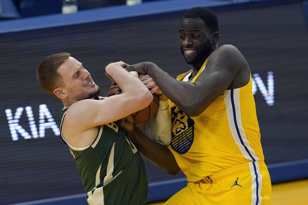 Milwaukee Bucks guard Donte DiVincenzo, left, tries to control the ball against Golden State Warriors forward Draymond Green during the first half of ...