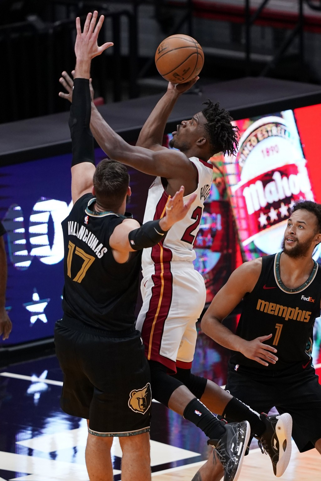Miami Heat forward Jimmy Butler (22) drives to the basket over Memphis Grizzlies center Jonas Valanciunas (17) and forward Kyle Anderson (1), during t...