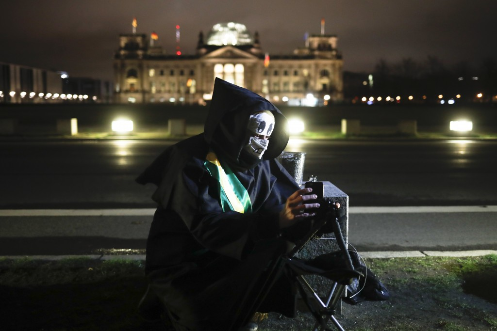 Brazilian activist and artist Rafael Puetter, dressed as the grim reaper, sits in front of the Reichstag and set up a live stream during a one-man pro...