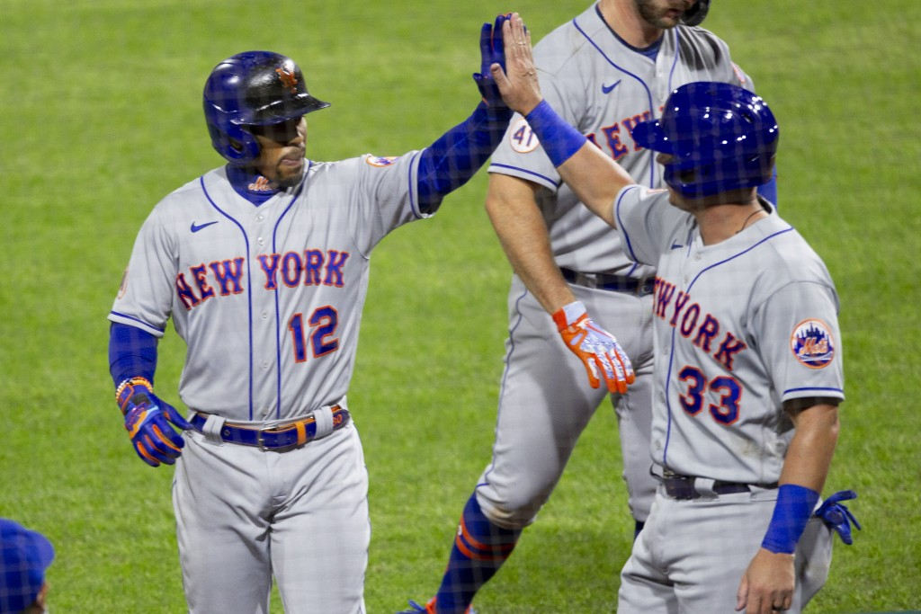 New York Mets Francisco Lindor (12) high fives James McCann (33) after McCann scored on Lindor's sacrifice fly during the seventh inning of a baseball...