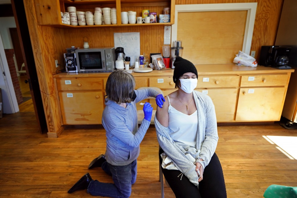Nurse Sharon Daley, administers a COVID-19 vaccination to Hollie Stanley in a makeshift clinic in the kitchen of a community center, Friday, March 19,...