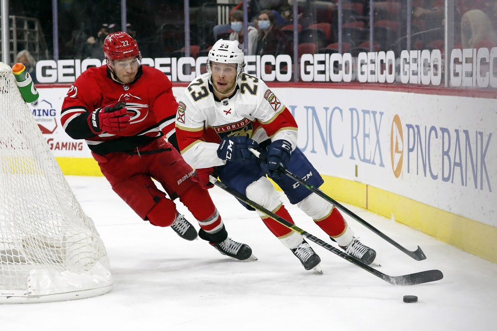 Florida Panthers' Carter Verhaeghe (23) is chased by Carolina Hurricanes' Brett Pesce (22) during the third period of an NHL hockey game in Raleigh, N...