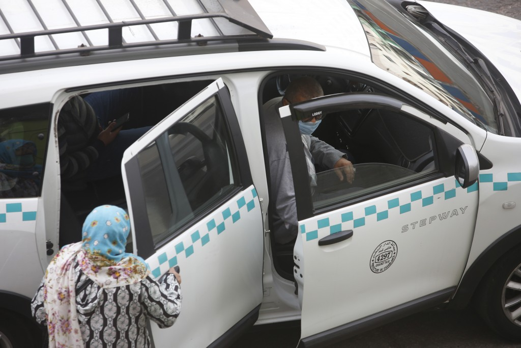 People wear face masks and take a taxi in Casablanca, Morocco, Tuesday, April 6, 2021. Moroccan authorities have announced the discovery of a new loca...