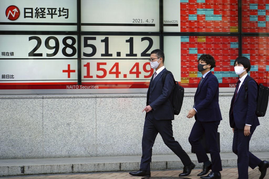 Men wearing protective masks walk in front of an electronic stock board showing Japan's Nikkei 225 index at a securities firm Wednesday, April 7, 2021...