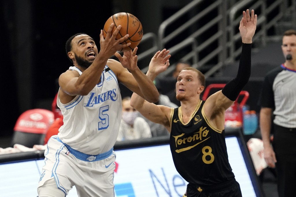 Los Angeles Lakers guard Talen Horton-Tucker (5) goes for a layup in front of Toronto Raptors guard Malachi Flynn (8) during the second half of an NBA...