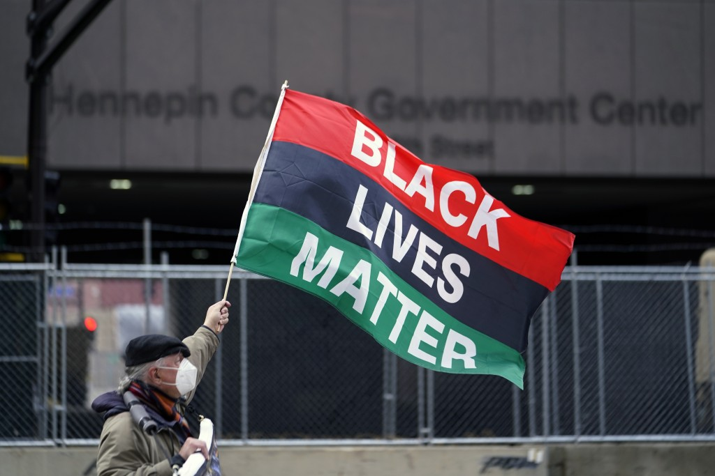 A protesters waves a Black Lives Matter flag across the street from the Hennepin County Government Center, Wednesday, April 7, 2021, in Minneapolis wh...
