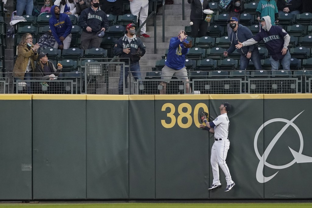 Seattle Mariners right fielder Mitch Haniger watches as a fan catches a three-run home run hit by Chicago White Sox's Zack Collin during the second in...