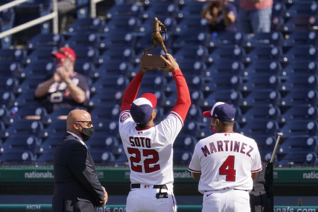 Washington Nationals right fielder Juan Soto (22) holds up his 2020 National League batting title trophy alongside general manager Mike Rizzo, left, a...