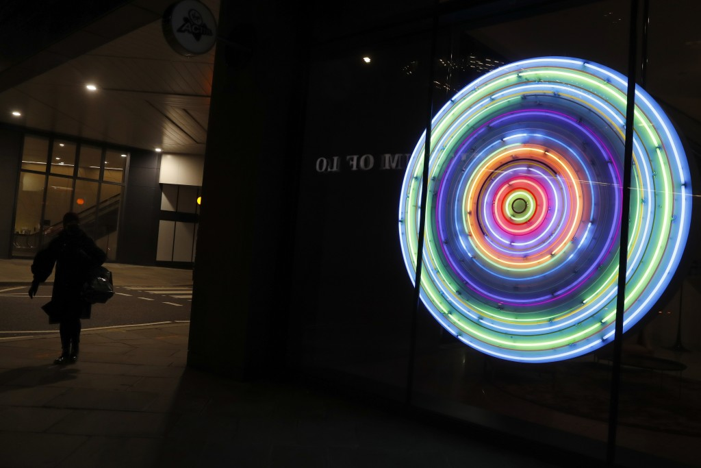 An illuminated sign adorns the front of an office building near the Barbican in the City of London, Saturday, March 6, 2021. (AP Photo/Alastair Grant)