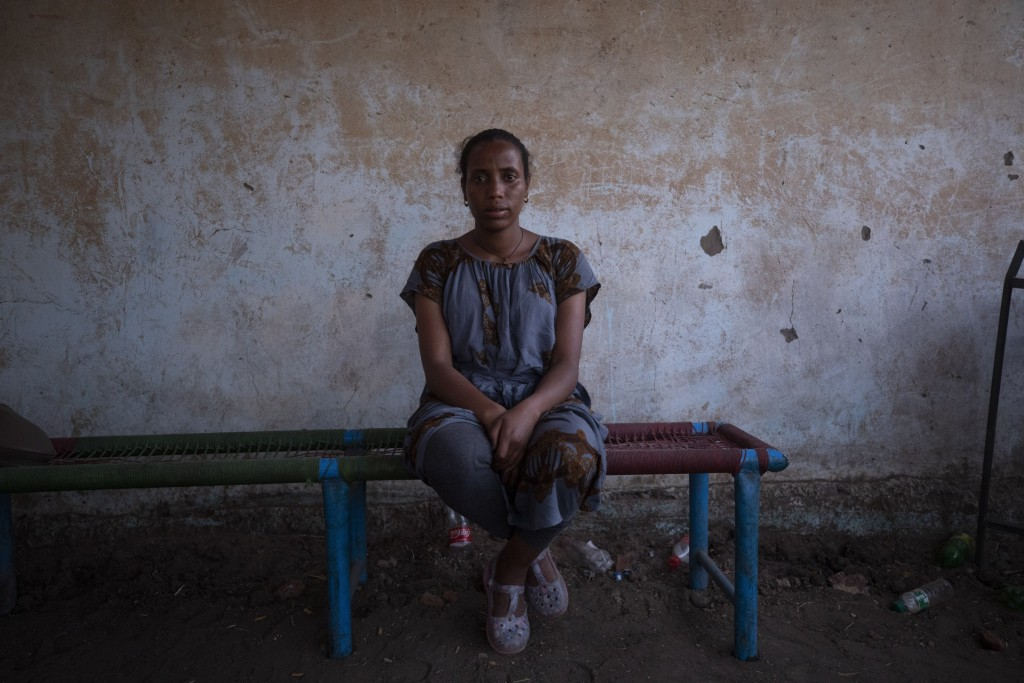 Elsa Tesfa Berhe, 26, center, a reproductive health official from Adwa, sits on a bench hours after arriving from Humera to Hamdayet, eastern Sudan, n...