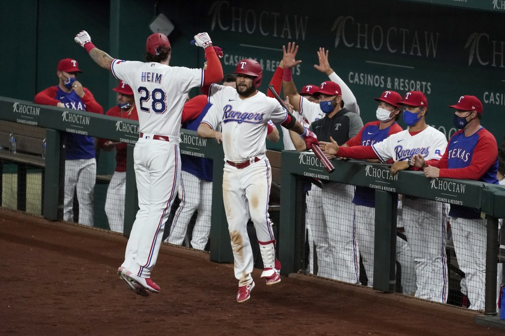 Texas Rangers' Jonah Heim (28) and Isiah Kiner-Falefa celebrate a solo home run by Heim during the sixth inning of the team's baseball game against th...