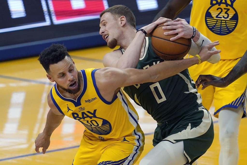 Milwaukee Bucks guard Donte DiVincenzo (0) is defended by Golden State Warriors guard Stephen Curry during the first half of an NBA basketball game in...