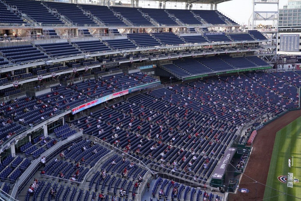 Fans sit socially distanced in the stands during an opening day baseball game between the Atlanta Braves and the Washington Nationals at Nationals Par...
