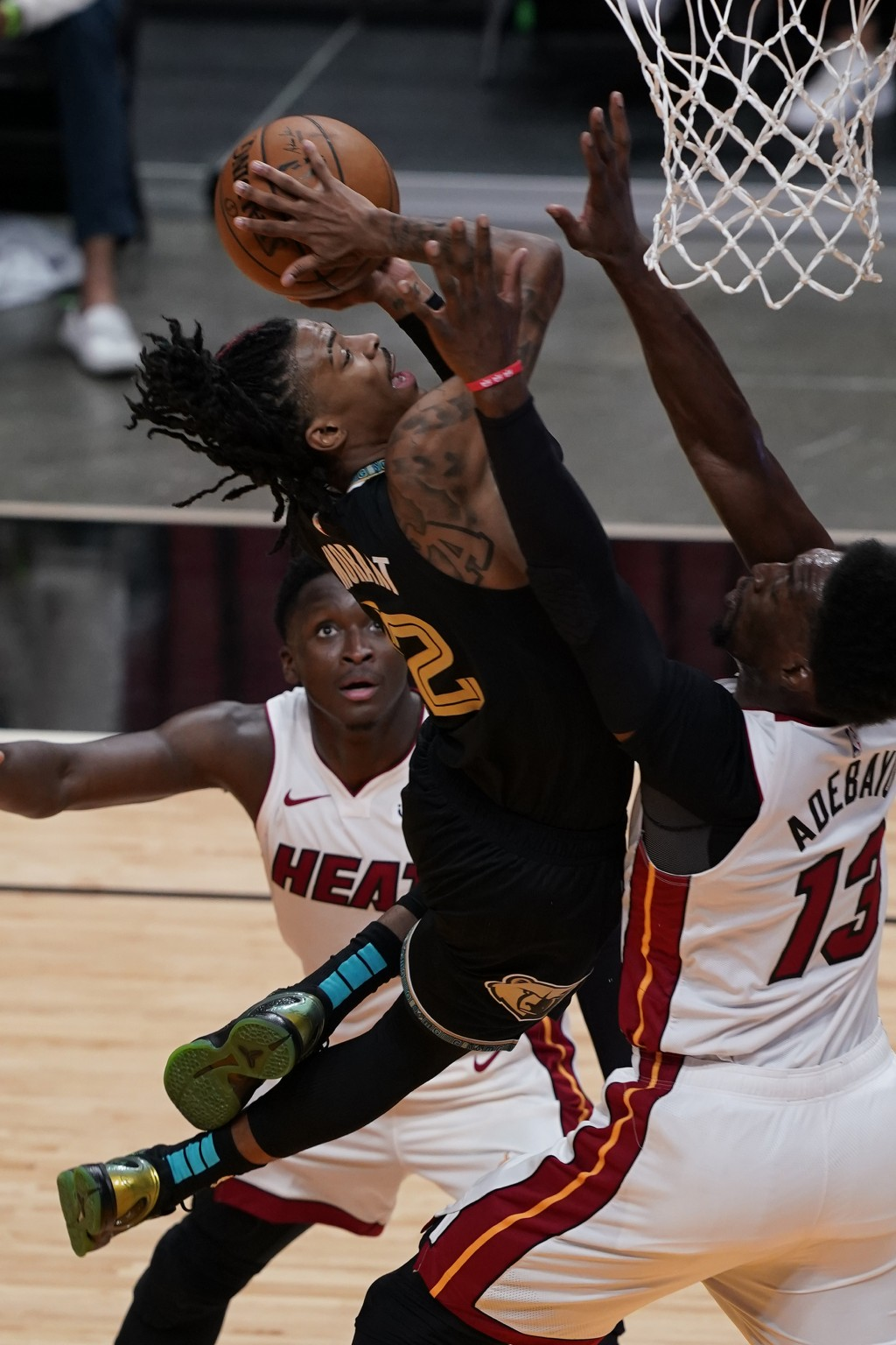 Memphis Grizzlies guard Ja Morant (12) drives to the basket as Miami Heat center Bam Adebayo (13) defends, during the second half of an NBA basketball...