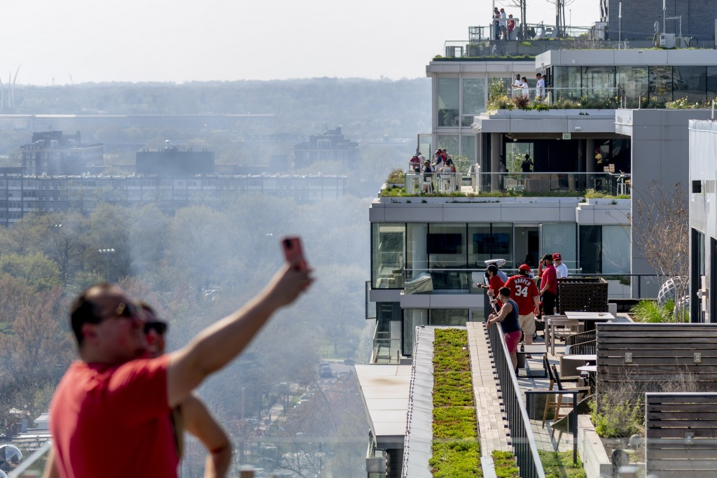 People gather on rooftops across the street from the stadium before the Washington Nationals play the Atlanta Braves in their opening day baseball gam...