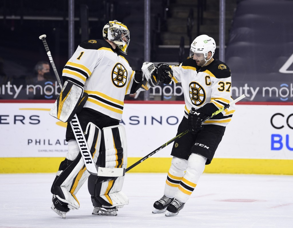 Boston Bruins' Patrice Bergeron, right, high-fives Jeremy Swayman after Bergeron scored a goal during the first period of an NHL hockey game against t...