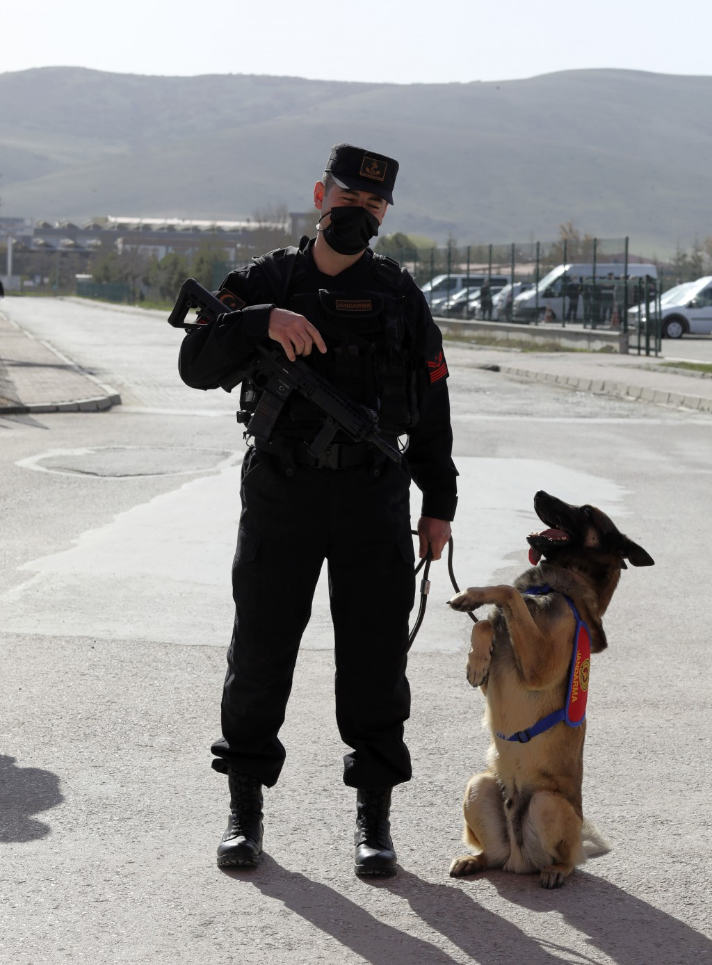 Bulent Okurcan, a military police officer stands with his 7-year-old Belgian wolf, Ihbar, as people wait outside a courthouse before the trial of 497 ...