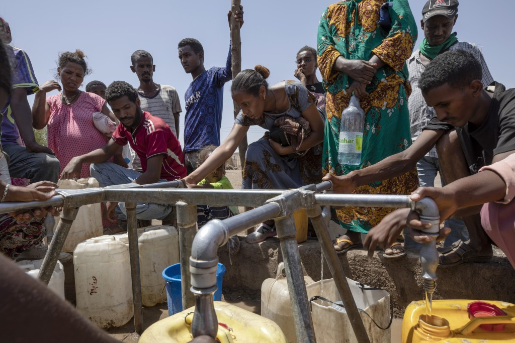 Elsa Tesfa Berhe, 26, center, a reproductive health official from Adwa, collects water a day after arriving from Humera to Hamdayet, eastern Sudan, ne...