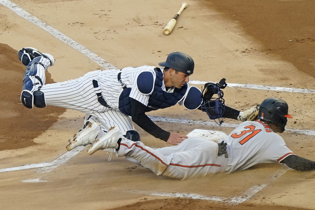 New York Yankees catcher Kyle Higashioka (66) tags Baltimore Orioles Cedric Mullins (31) out at the plate on a fielder's choice during the first innin...