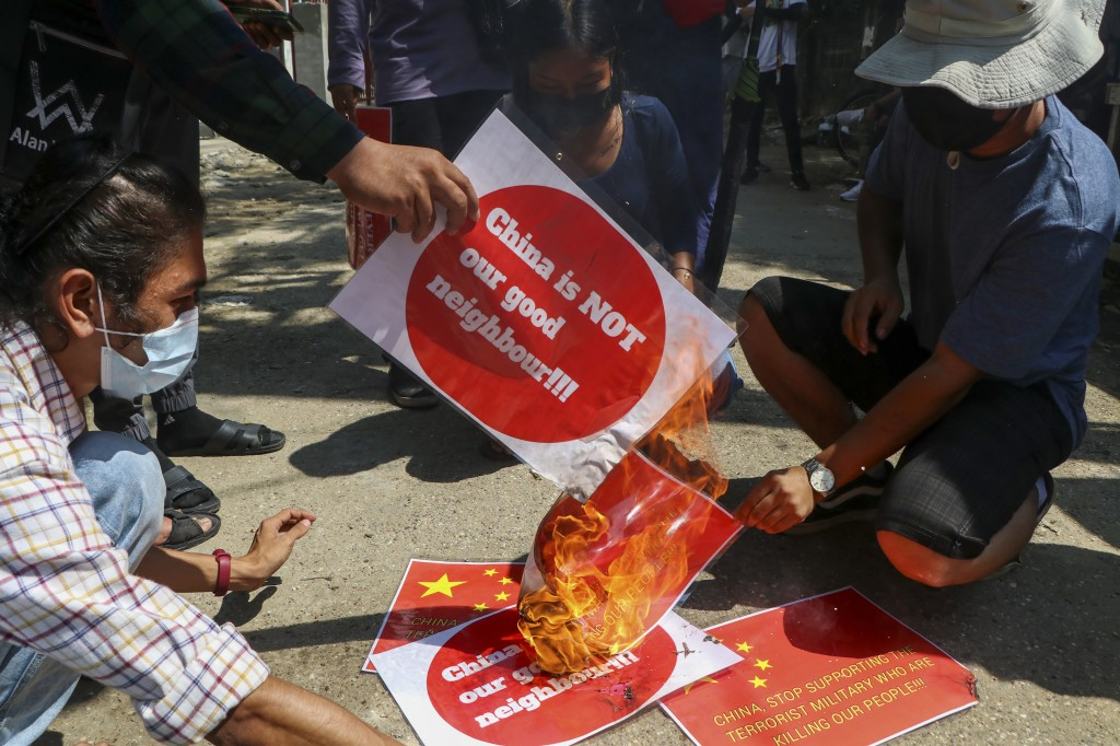 Anti-coup protesters burn a representation of the Chinese national flag during a demonstration in Yangon, Myanmar on Wednesday, April 7, 2021. Threats...