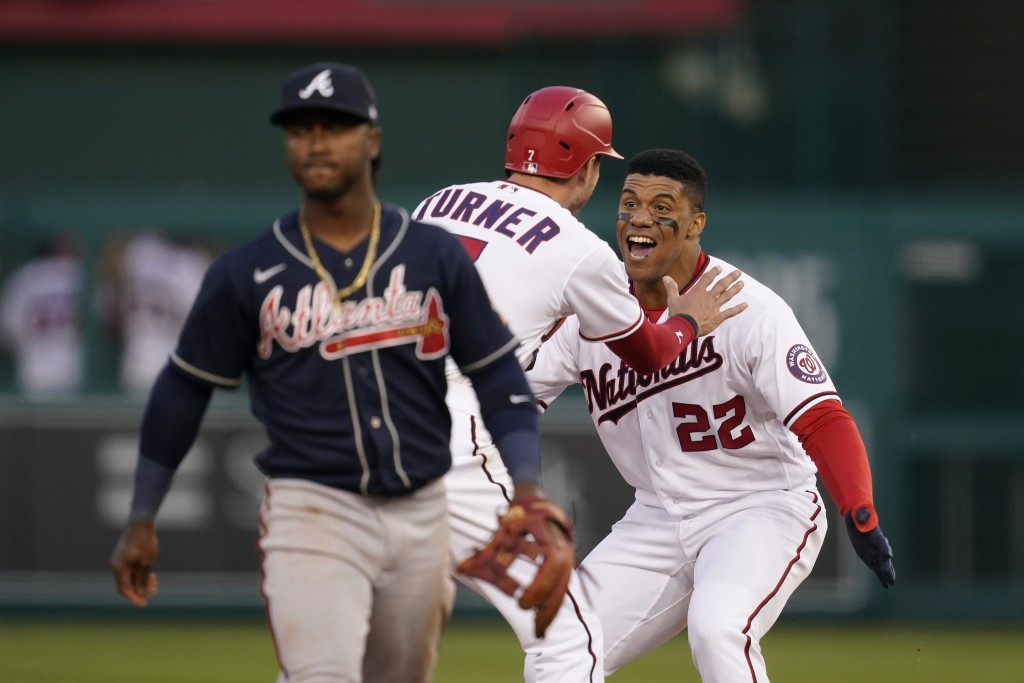 Washington Nationals' Juan Soto (22) and Trea Turner celebrate in front of Atlanta Braves second baseman Ozzie Albies after Soto hit a game-winning si...