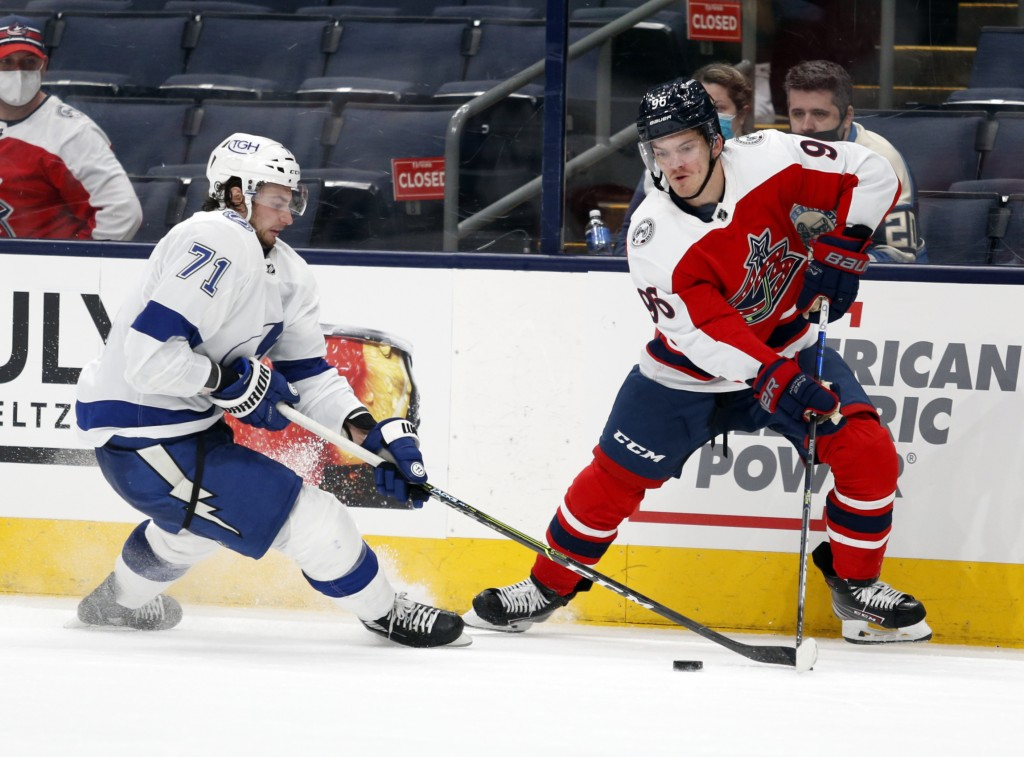 Columbus Blue Jackets forward Jack Roslovic, right, reaches for the puck against Tampa Bay Lightning forward Anthony Cirelli during the second period ...